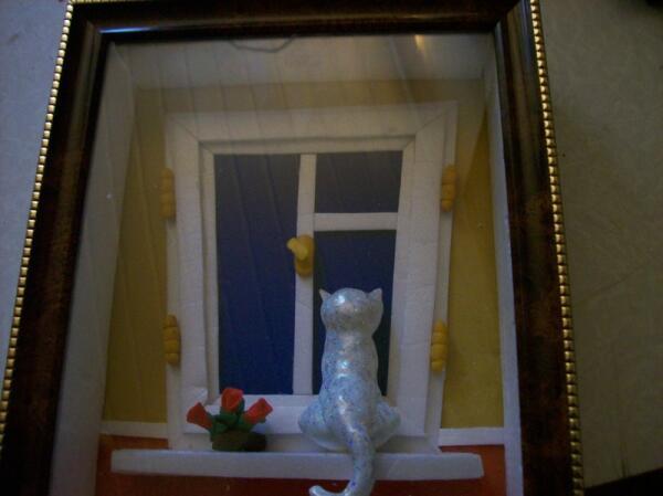 Кошка на подоконнике в рамке за стеклом