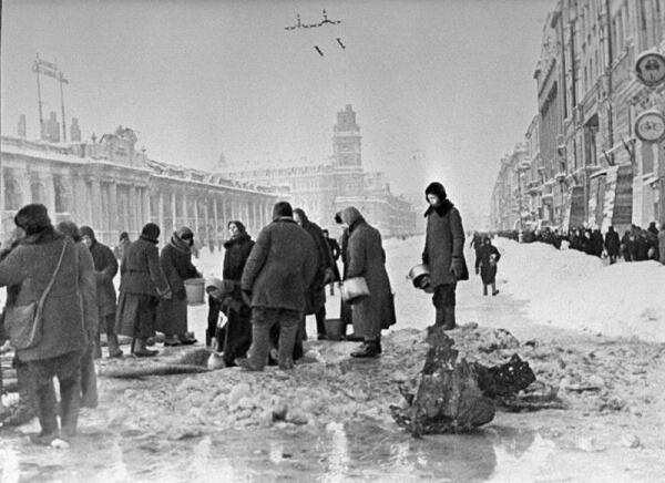 Жители блокадного Ленинграда набирают воду, появившуюся после артобстрела в пробоинах в асфальте.