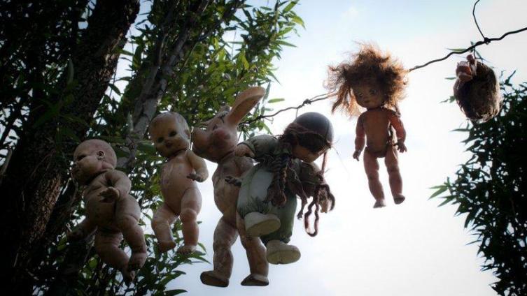 Здесь повсюду развешаны старые куклы