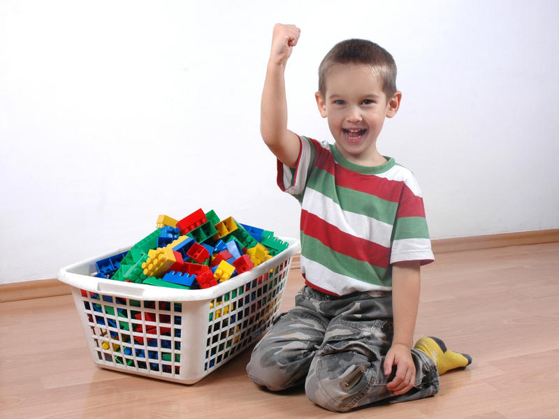 child tidies up toys photo