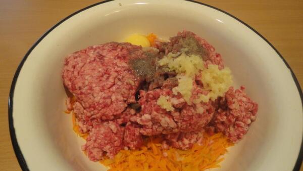 Выкладываем фарш в миску, добавляем  зажарку, вбиваем сырое яйцо, выдавливаем пару зубчиков чеснока, перчим, присаливаем...