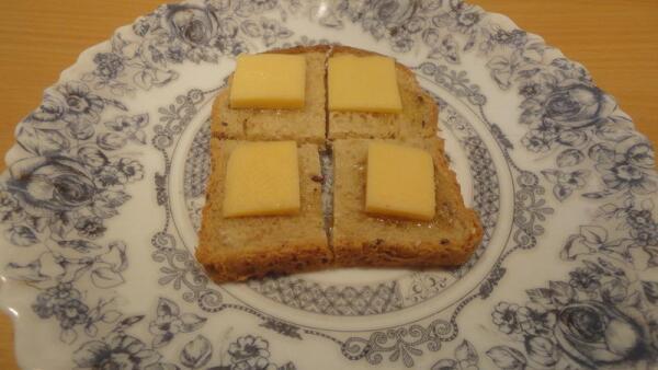 Режем кусочек хлеба на четыре части, каждую из которых присаливаем, чуть сбрызгиваем растительным маслом, сверху кладем тоненький ломтик твердого сыра