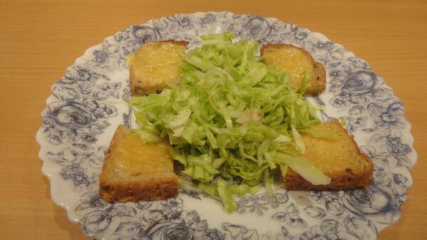 Выкладываем капусту на тарелку с прожаренными ломтиками хлеба