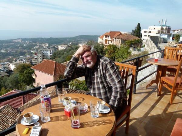 За столиком ресторана с видом на город Крую, лежащий где-то далеко внизу и его окрестности