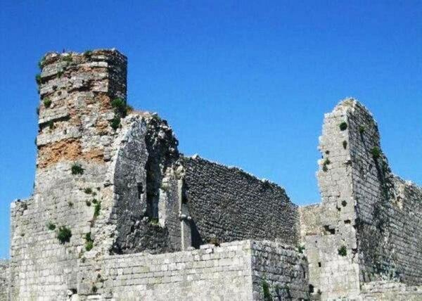За крепостными стенами стоят здания на разной стадии разрушения