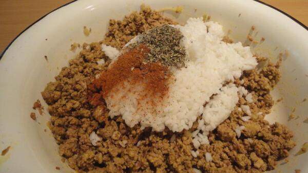 Добавляем к фаршу рис, молотый красный перец (паприку), пряные травы…