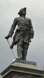 Правой рукой Петр I опирается на трость, в левой он держит подзорную трубу
