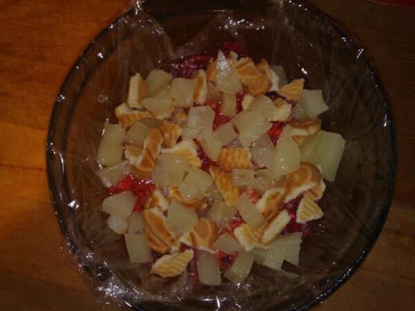 Слоями выложить в застеленную пищевой пленкой форму желе, фрукты и печенье (бисквит).