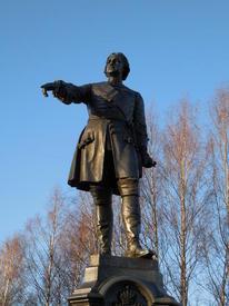 В отличие от правой, указующей, левая рука императора опущена. В ней он держит свиток
