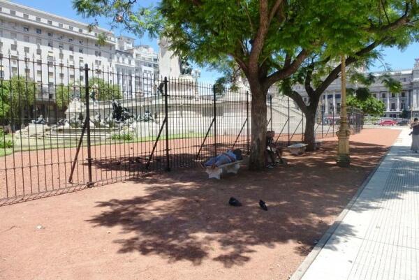 Бездомные отдыхают в тени деревьев