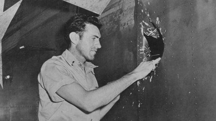 Первый лейтенант Замперини осматривает пробоину в своём бомбардировщике B-24 Liberator, сделанную над Науру, 18 апреля 1943 года.