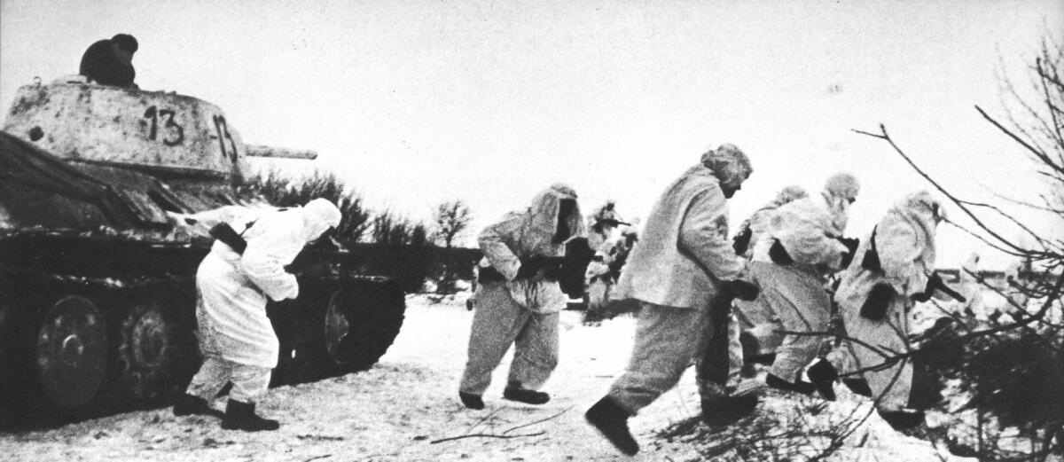 Документальное фото, советские солдаты в зимних маскировочных костюмах десантируются с танков Т-34/76