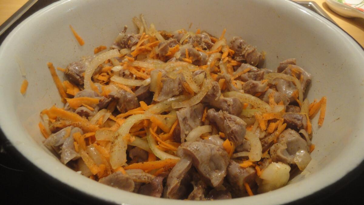 Добавляем к желудкам пошинкованную полукольцами луковицу и тертый на крупной терке корнеплод моркови, перемешиваем