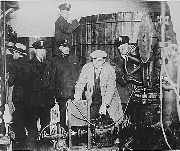Полиция Детройта осматривает оборудование для производства спиртного в нелегальной пивной в эпоху «сухого закона»