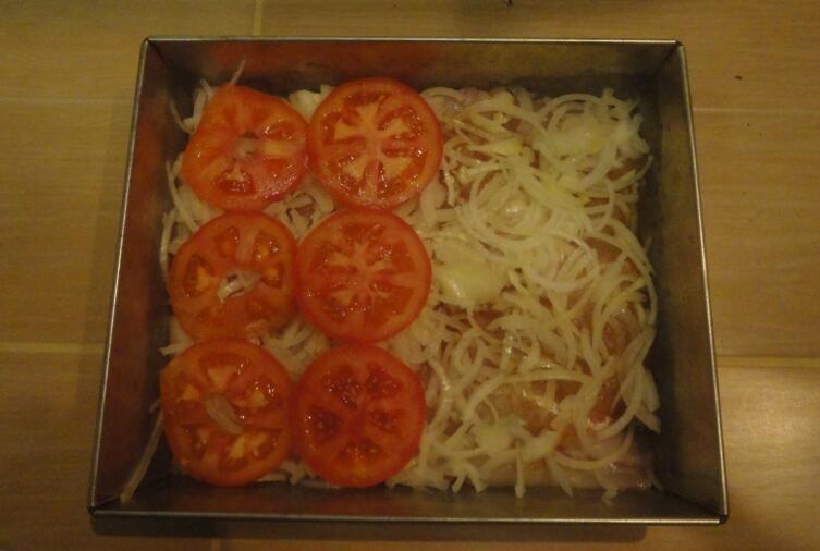 Поверх судака укладываем шинкованный лук, а уже на него - помидоры, порезанные кружками
