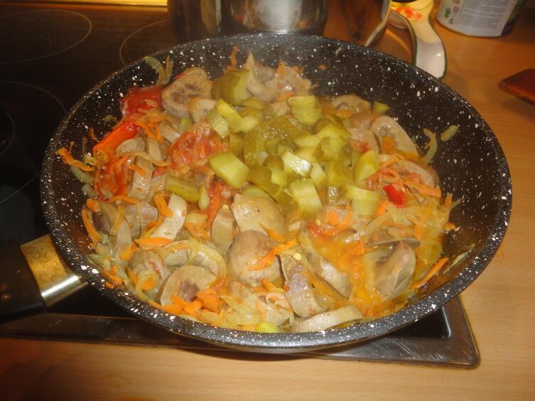 За чесноком, томатной пастой и аджикой отправляем порезанные на некрупные кубики соленые огурцы...