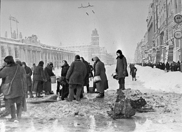Жители блокадного Ленинграда набирают воду, появившуюся после артобстрела в пробоинах в асфальте на Невском проспекте, фото Б. П. Кудоярова, декабрь 1941