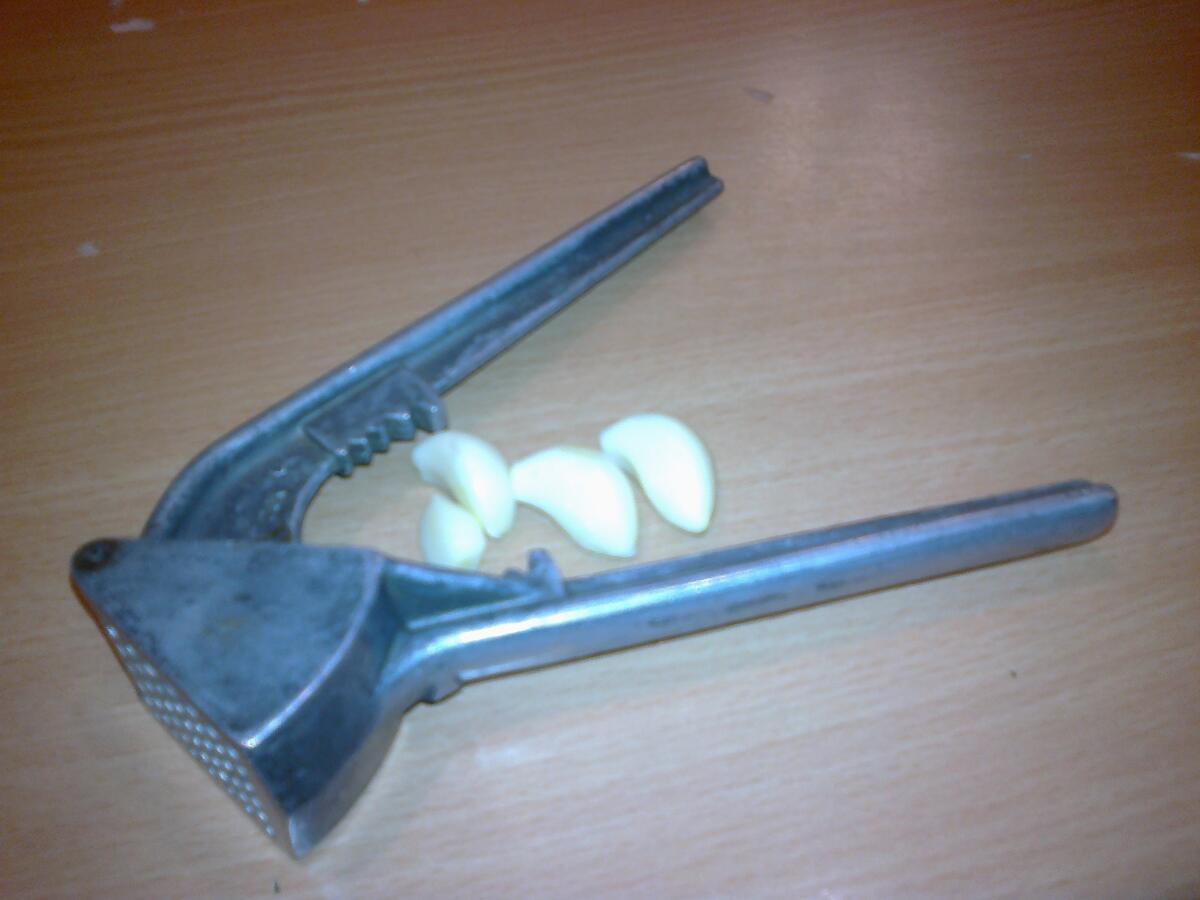Выдавливаем в миску 3-4 зубчика чеснока