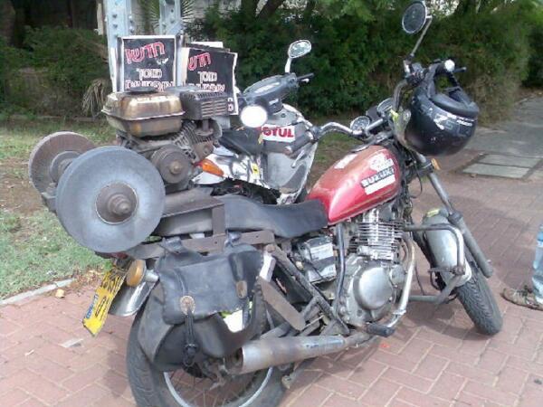 Современный уличный точильщик: на мотоцикле смонтирован небольшой бензиновый мотор, шпиндель с двумя кругами (один - шлифовальный, другой - абразивный)