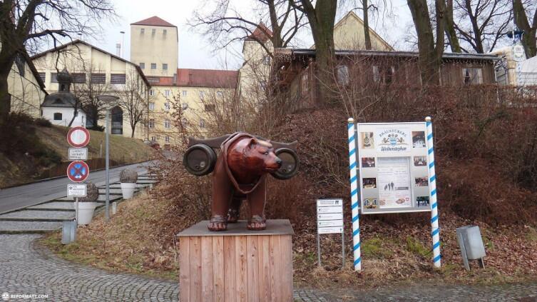 Деревянная статуя медведя, навьюченного парой больших пивных бочек