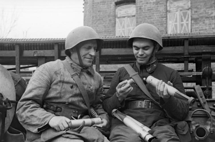 Московский пожарный показывает своему товарищу обезвреженные немецкие зажигательные бомбы