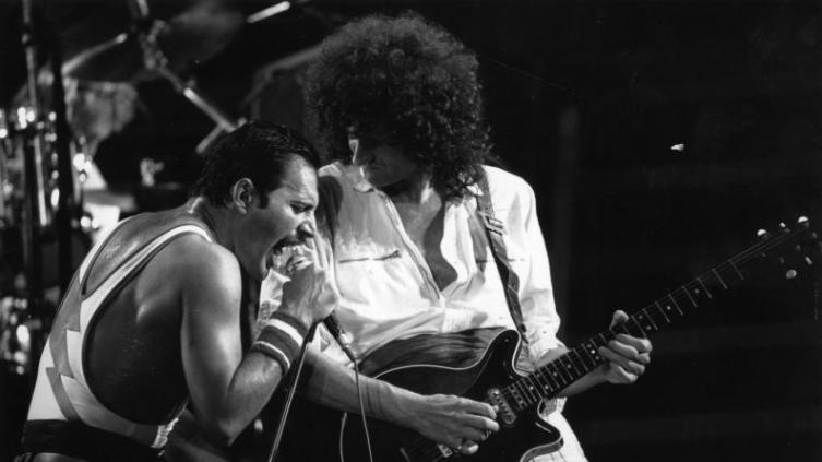 Гитарист Брайан Мэй, певец Фредди Меркьюри и рок-группа «Queen» во время концерта