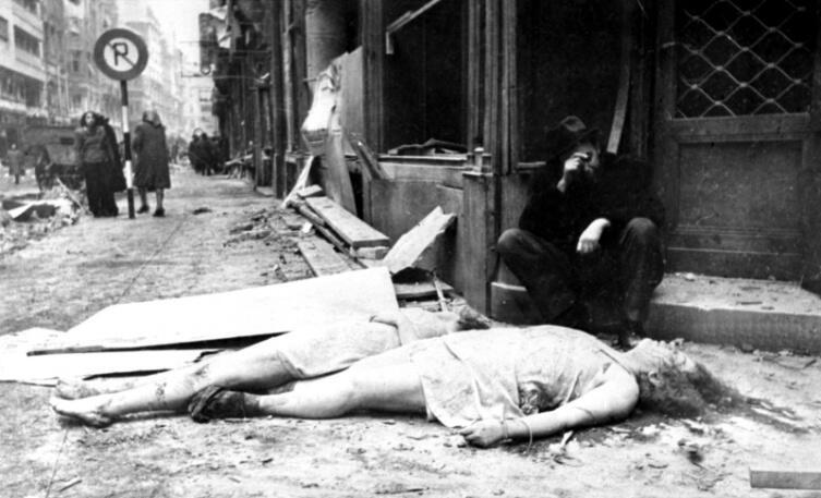 Мужчина возле тел убитых женщин в освобожденном будапештском гетто. Более 220 тысяч будапештских евреев при фашистском режиме были перемещены в гетто