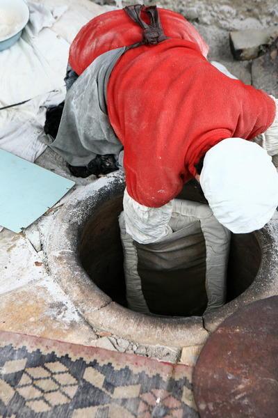 Ловко помещают подушку в печь и прикрепляют лист к стенке печки