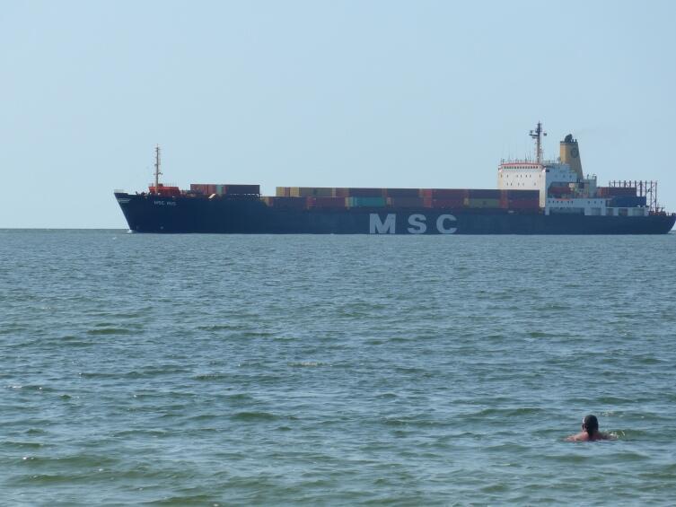 Контейнеровоз подходит ко входу в залив, снимок с берега Мельнраге