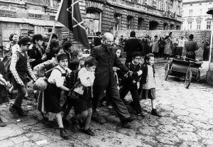 Старый доктор шел во главе колонны поющих детей, держа на руках ослабевшего мальчика, а за руку – девочку.