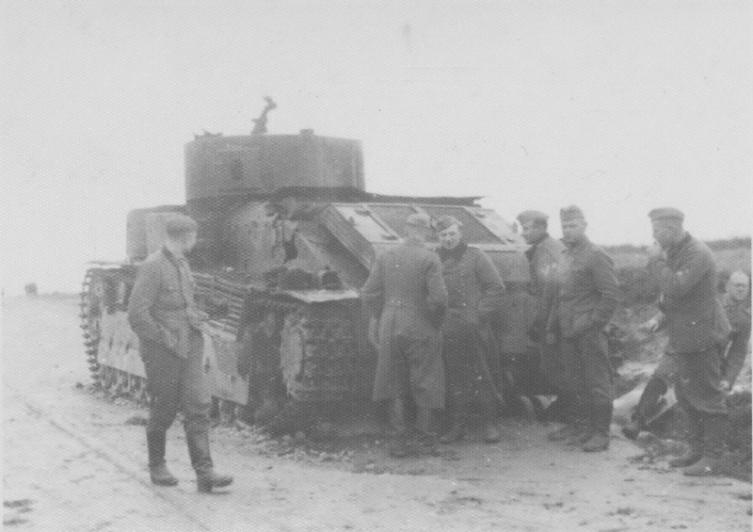 Немецкие солдаты рассматривают подбитый и сгоревший советский танк Т-28