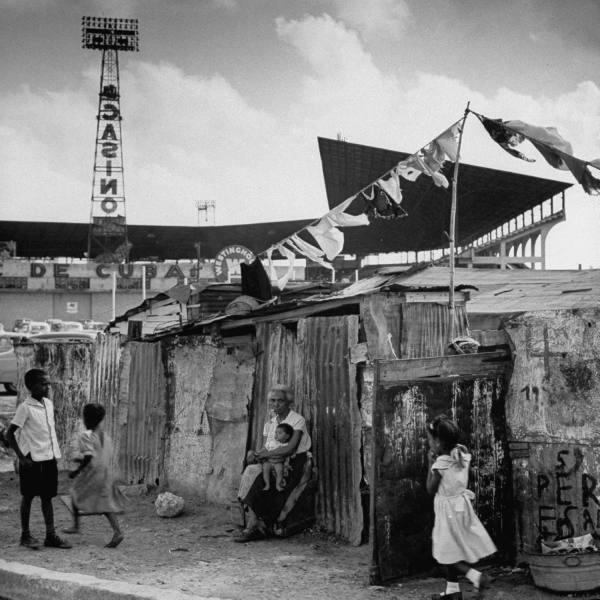 Трущобы в Гаване, неподалеку от бейсбольного стадиона. На заднем плане реклама близлежащего казино, 1954 г.