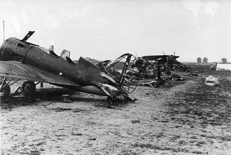 """Советский аэродром после немецкого авианалёта во время операции """"Барбаросса"""". Несколько сгоревших учебных И-16 УТИ-4 и немецкий Henschel Hs 126"""