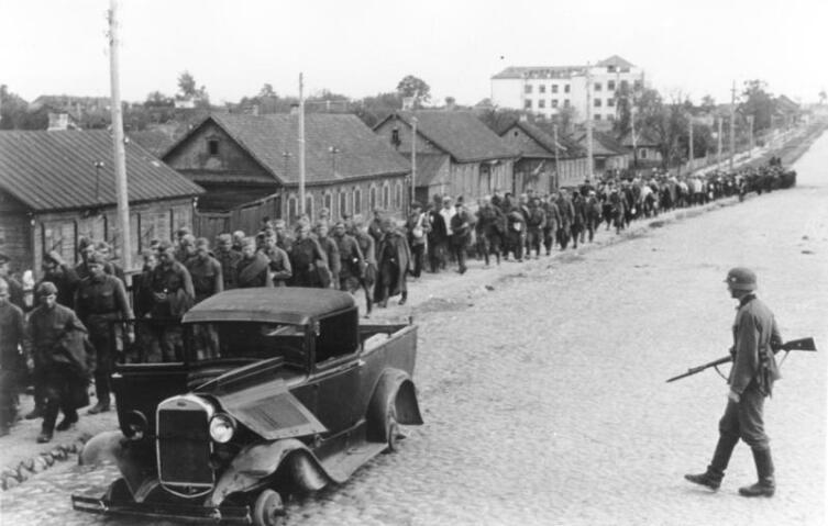 Колонна советских военнопленных и разбитый автомобиль ГАЗ-4 на улицах Минска, 2 июля 1941 г.