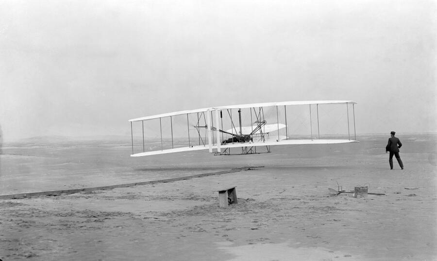 Первый полёт Флайера-1 17 декабря 1903 года, пилотирует Орвилл, Уилбур — на земле. Фотография Джона Т. Дэниелса со спасательной станции Килл Дэвил Хиллс, использован фотоаппарат Орвилла на треножнике