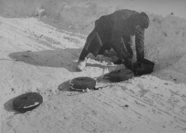 Немецкий сапер минирует дорогу во время отступления под Москвой
