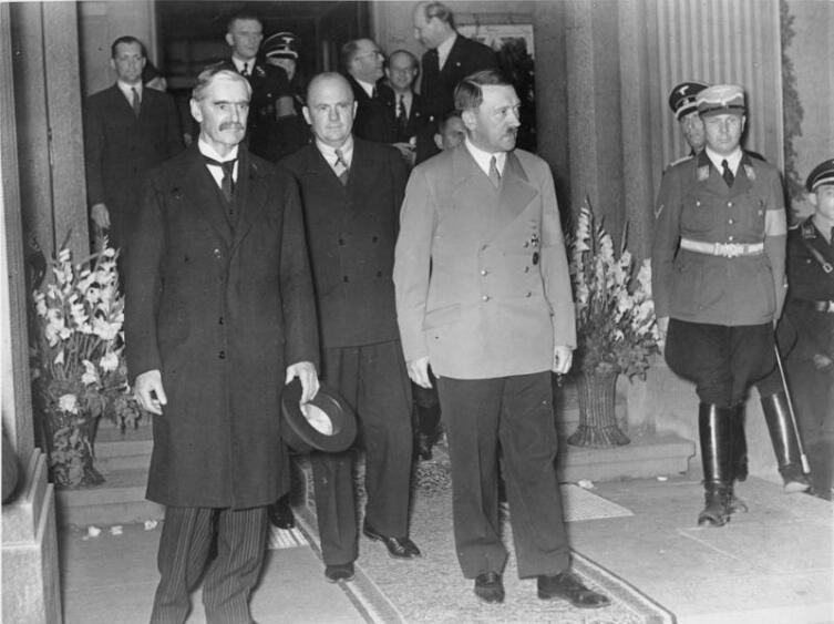 Чемберлен (слева) и Гитлер на встрече в Бад-Годесберге, 23 сентября 1938 года. В середине главный переводчик доктор Пауль Шмидт