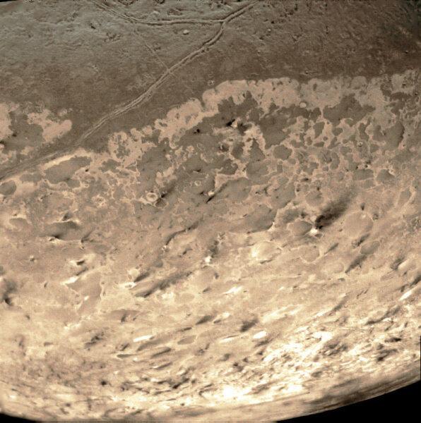 Снимок Тритона, сделанный «Вояджером-2» в 1989 году. Тёмные струи — следы извержений криовулканов