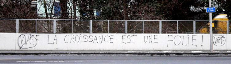 Антиглобалистское граффити в Лозанне: зачёркнута эмблема Всемирного экономического форума (WEF) и прибавлены слова: «Рост — это безумие!»