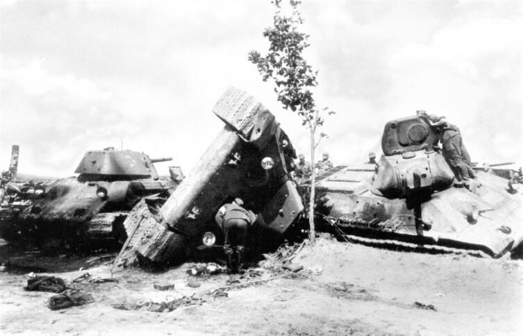 Солдаты вермахта осматривают танки Т-34 32-й танковой дивизии РККА, попавшие под авиаудар на дороге в районе Язова Старого