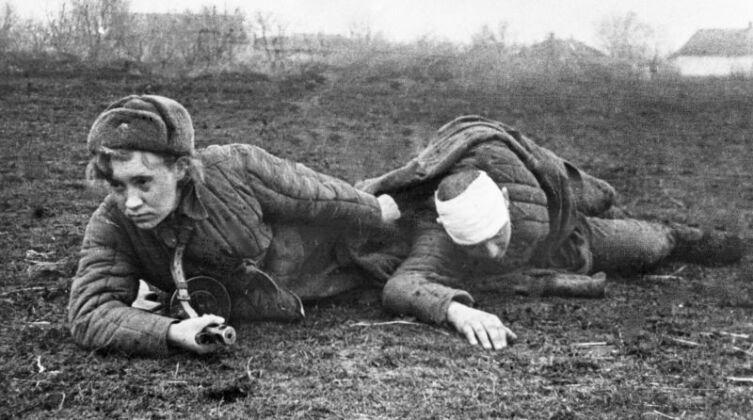 Санинструктор сержант В. Грибкова эвакуирует раненого с поля боя на Украине