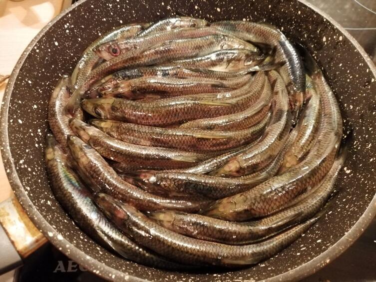 Плотно укладываем рыбку к рыбке брюшками вниз в глубокую сковородку