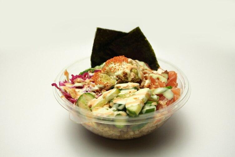 Чаша с поке. В блюде есть рис, суши, маринованная капуста, огурец, тобико, морские водоросли