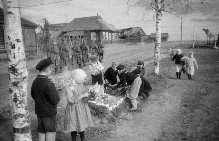 Дети возлагают цветы на могилы советских бойцов, павших в боях за освобождение Ржева