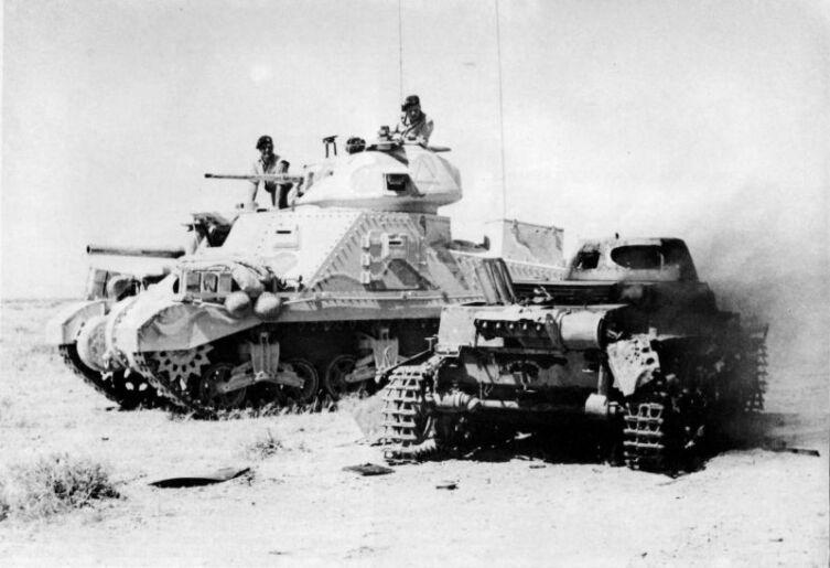 Британские танкисты проезжают на танке М3 «Грант» мимо подбитого немецкого танка Pz.I