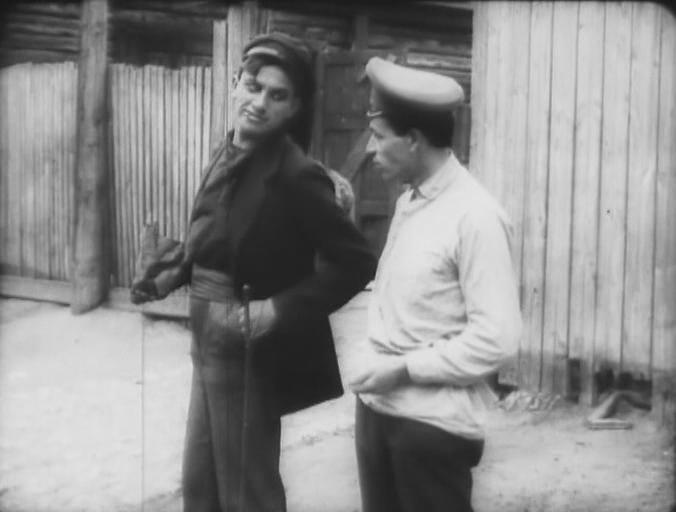Хулиган (В. В. Маяковский) отбирает у прохожего кулёк с семечками. Кадр из фильма «Барышня и хулиган», 1918 г.
