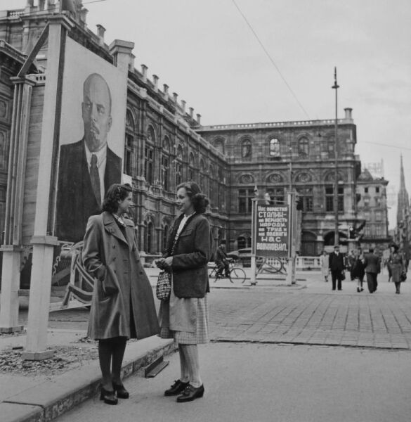 Австрийские девушки Оппольцер и Анита Стефаннели разговаривают рядом с портретом В.И. Ленина у здания Государственной оперы в Вене. В центре кадра находится плакат с цитатой из Государственного гимна СССР