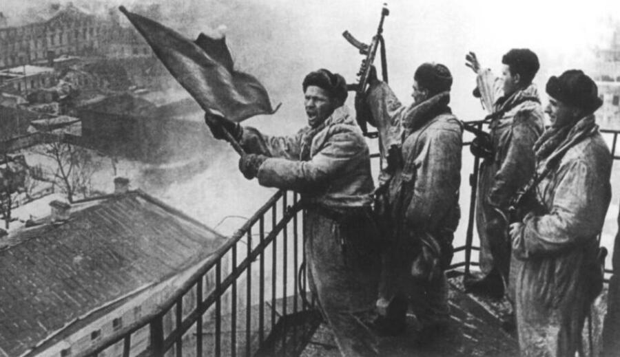 Советские солдаты поднимают красный флаг над освобожденной Гатчиной, 26 января 1944 г.