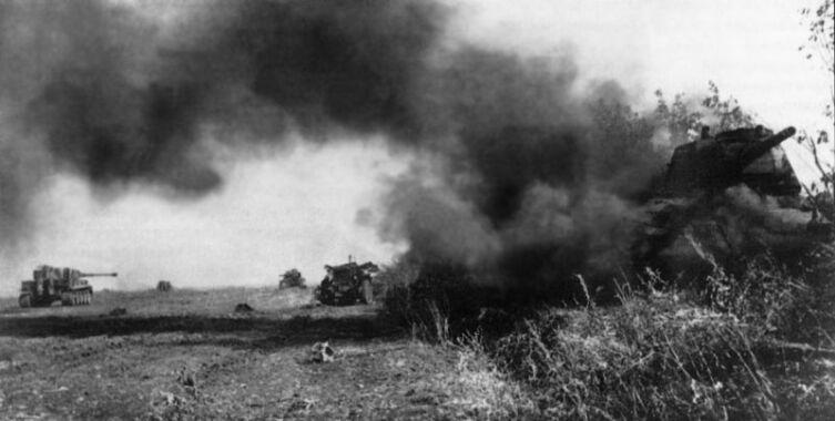 Поле боя на Курской дуге. На переднем плане справа подбитый советский танк Т-34, дальше у левого края фото — немецкий Pz.Kpfw. VI «Тигр», вдалеке — еще один Т-34. Курская дуга, лето 1943 г.
