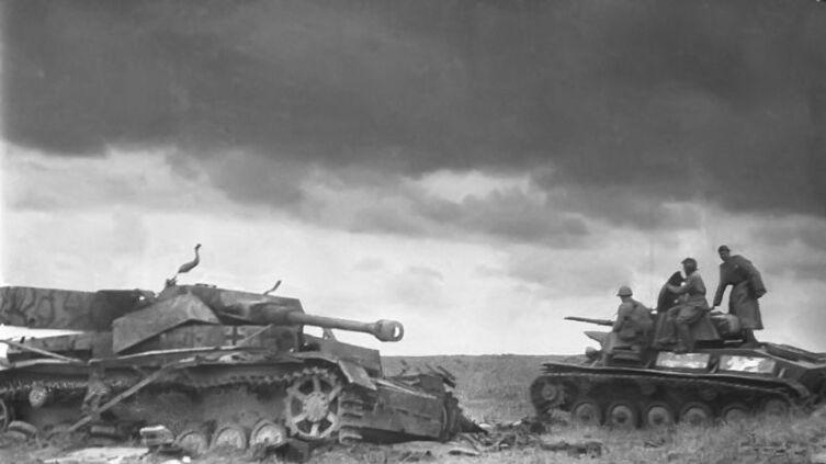 Советский легкий танк Т-70 проходит мимо уничтоженного немецкого среднего танка Pz.Kpfw. IV. Курская дуга